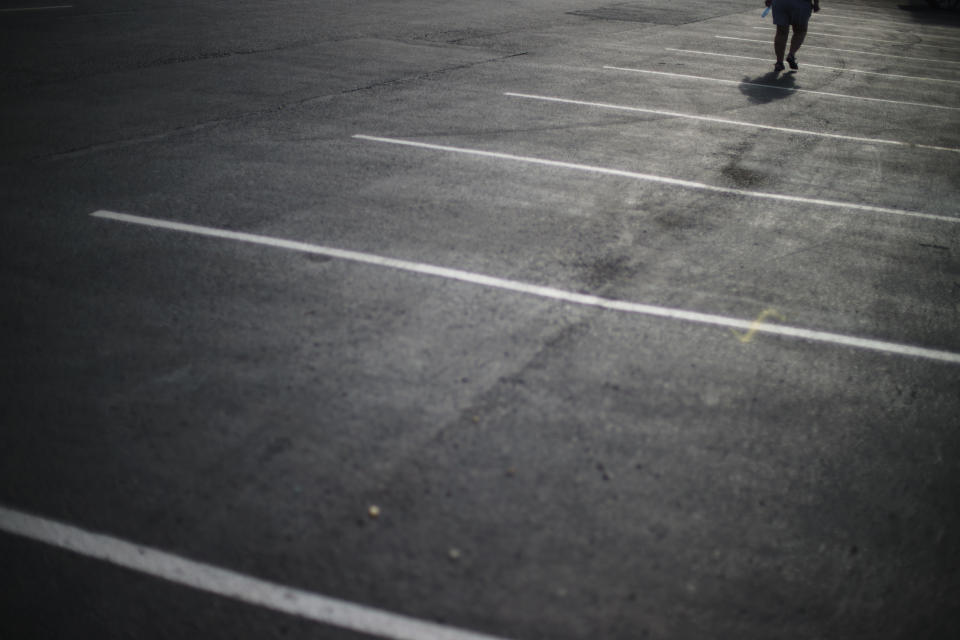 A customer walks through the parking lot of a Starbucks coffee shop in Lake City, Fla., Friday, April 16, 2021. In 2015, a klansman working as an informant for the FBI met with fellow klansmen outside the coffee shop about murdering a Black former inmate from the prison where some of them worked as prison guards. (AP Photo/David Goldman)