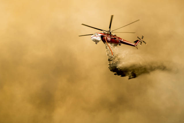 <p>Helicopters pass through smoke from the holy fire burning through Orange and Riverside county that has increased to over 18,000 acres in Lake Elsinore, Calif., on Aug. 10, 2018. (Photo: Maria Alejandra Cardona/Los Angeles Times via Getty Images) </p>