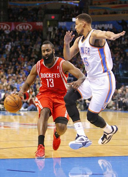 Houston Rockets guard James Harden, left, drives to the basket around Oklahoma City Thunder guard Thabo Sefolosha, right, during the first quarter of an NBA basketball game, Sunday, Dec. 29, 2013, in Oklahoma City. (AP Photo/Alonzo Adams)