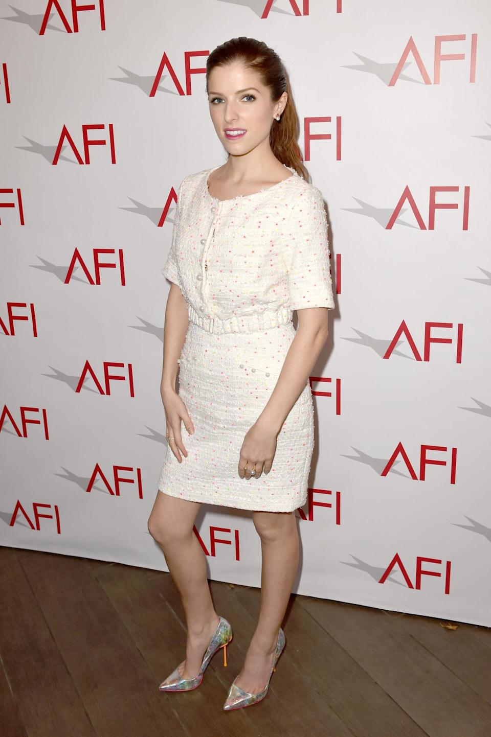 Anna Kendrick paired a lady-like bouclé mini dress with metallic shining heels to make her look a little more fun and young.