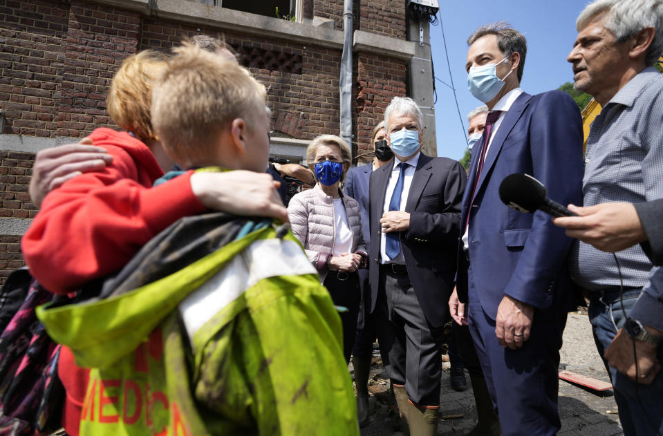 European Commission President Ursula von der Leyen, center left, and Belgian Prime Minister Alexander de Croo, second right, speak with Madeline Brasseur, 37, Paul Brasseur, 42, and their son Samuel, 12 after flooding in Pepinster, Belgium, Saturday, July 17, 2021. Residents in several provinces were cleaning up after severe flooding in Germany and Belgium turned streams and streets into raging torrents that swept away cars and caused houses to collapse. (AP Photo/Virginia Mayo)