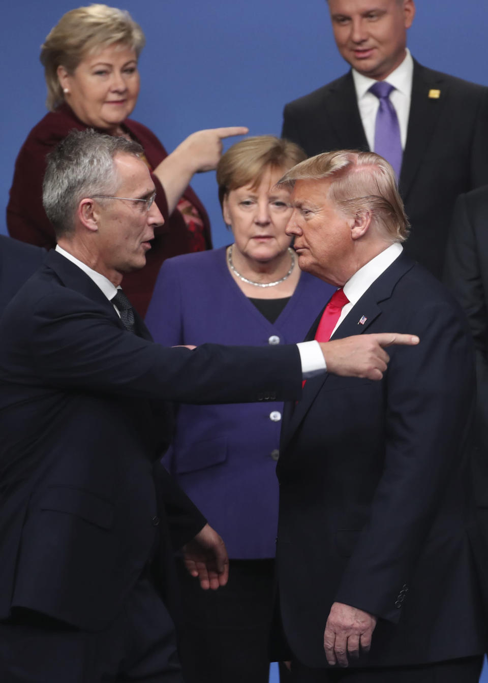 NATO Secretary General Jens Stoltenberg, left, speaks with U.S. President Donald Trump, right, after a group photo at a NATO leaders meeting at The Grove hotel and resort in Watford, Hertfordshire, England, Wednesday, Dec. 4, 2019. NATO Secretary-General Jens Stoltenberg rejected Wednesday French criticism that the military alliance is suffering from brain death, and insisted that the organization is adapting to modern challenges. (AP Photo/Francisco Seco)