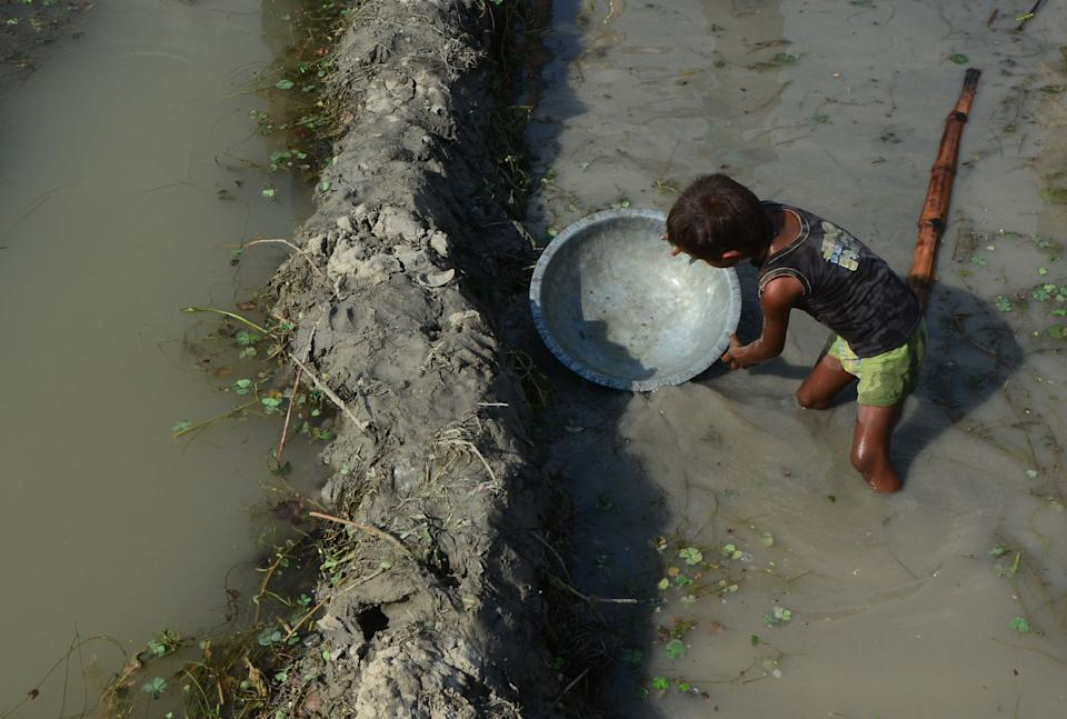 An indian local boy fixes mud to collect remaining water of shrunken Varuna River, in Phoolpur village, some 45 kms from Allahabad on June 8, 2019. Much of India has been suffering from a heat wave for weeks along with a severe drought that has decimated crops, killed livestock and left at least 330 million Indians without enough water for their daily needs. (Photo by Ritesh Shukla ) (Photo by Ritesh Shukla/NurPhoto via Getty Images)