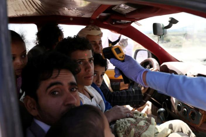 FILE PHOTO: A health worker takes the temperature of people riding a taxi van, amid concerns of the spread of the coronavirus disease (COVID-19), at the main entrance of Sanaa, Yemen