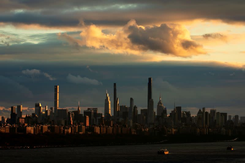 FILE PHOTO: Barges sit at anchor on Hudson River as sunset falls on skyline of west side of Manhattan in New York