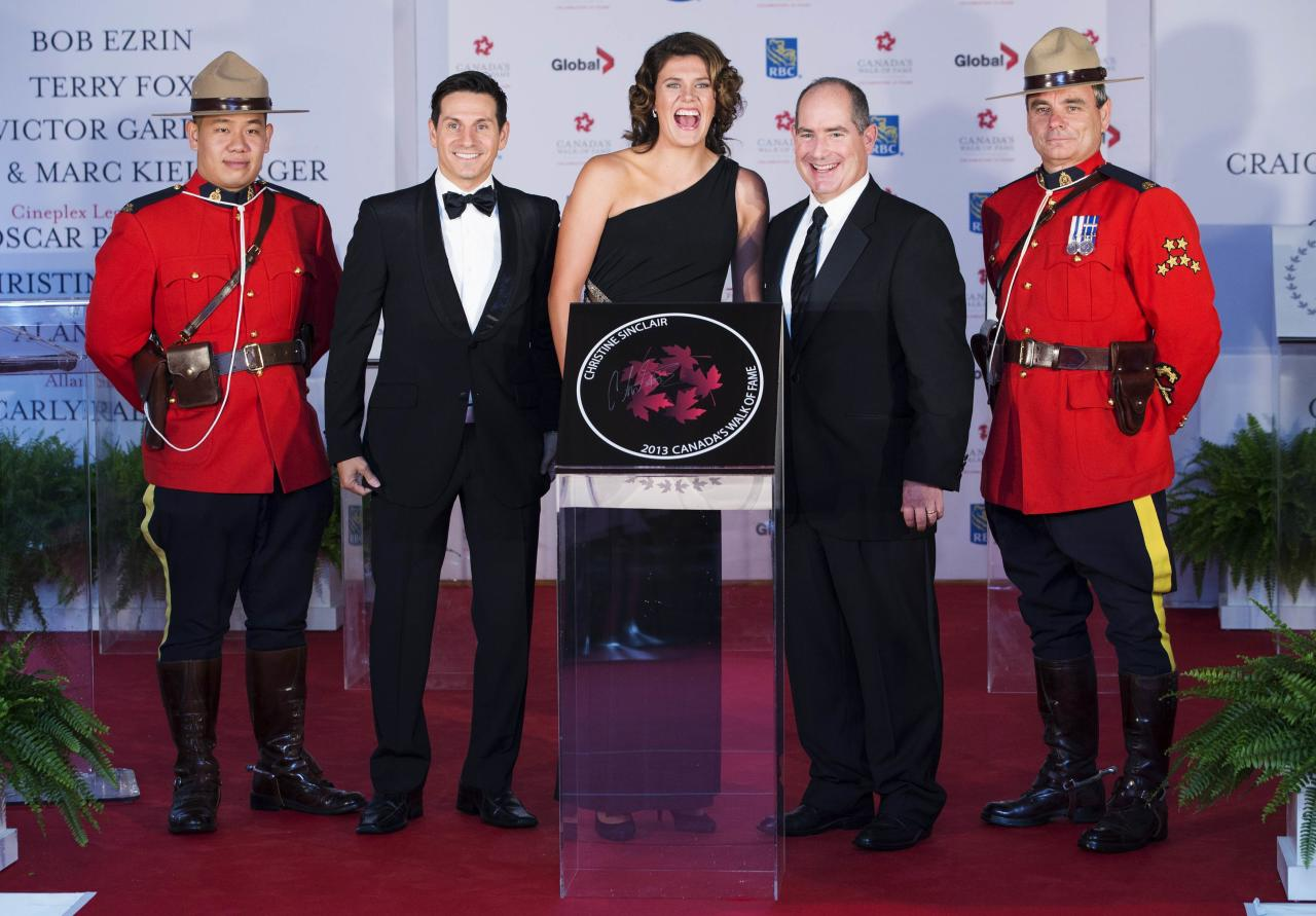 Soccer player Christine Sinclair (C) stands near her star with host Rick Campanelli (2nd L), Cineplex Chief Operating Officer Dan McGrath (2nd R), and two Royal Mounted Police Officers during Canada's Walk of Fame induction ceremonies in Toronto, September 21, 2013. REUTERS/Mark Blinch (CANADA - Tags: ENTERTAINMENT SPORT BUSINESS)
