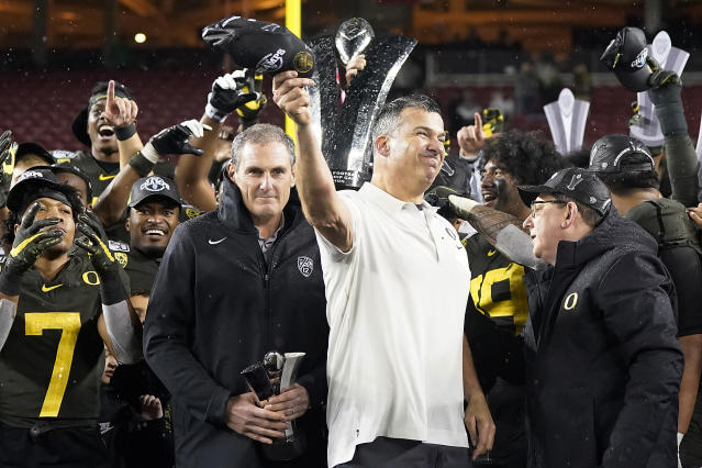 Oregon coach Mario Cristobal celebrate after Oregon defeated Utah 37-15 in the Pac-12 Conference championship NCAA college football game in Santa Clara, Calif., Friday, Dec. 6, 2018. (AP Photo/Tony Avelar)