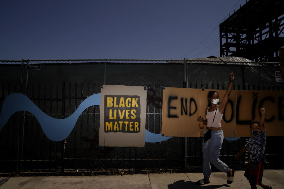 FILE - In this Aug. 28, 2020, file photo, a woman and a boy raise their hands as vehicles participating in a caravan protest against racial injustice pass by them in Los Angeles. Almost six months after the death of George Floyd, criminal justice reform advocates are cheering multiple victories in the 2020 election. (AP Photo/Jae C. Hong, File)
