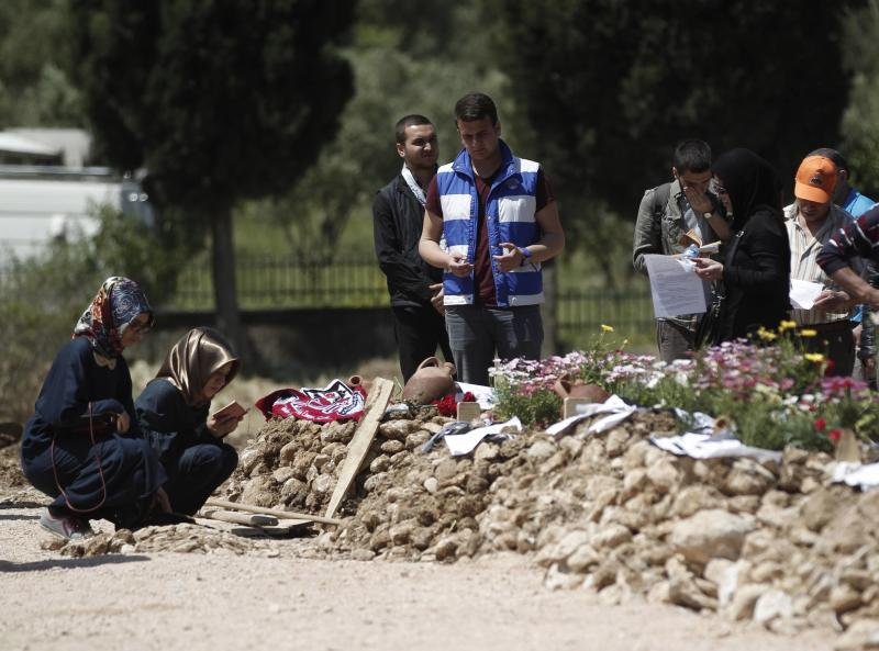 People mourn at graves for miners who died in Tuesday's mine disaster, at a cemetery in Soma, a district in Turkey's western province of Manisa