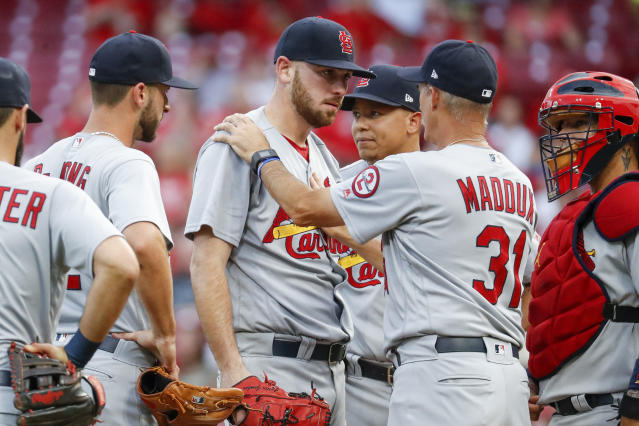 St. Louis Cardinals starting pitcher Austin Gomber, center, meets with pitching coach Mike Maddux (31) during the third inning of the team's baseball game against the Cincinnati Reds, Tuesday, July 24, 2018, in Cincinnati. (AP Photo/John Minchillo)