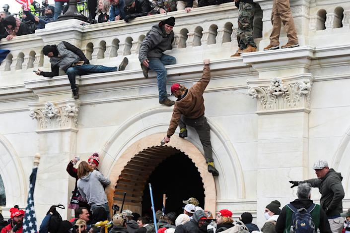 """Rioters climb the walls of the U.S. Capitol after President Trump encouraged a rally audience to pressure Republican lawmakers.<span class=""""copyright"""">Stephanie Keith—Reuters</span>"""