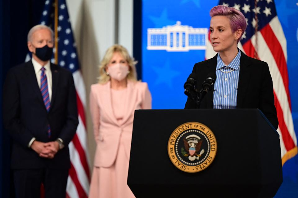 US soccer player Megan Rapinoe (R) speaks, flanked by US President Joe Biden (L) and First Lady Jill Biden during an Equal Pay Day event in the South Court Auditorium of the White House in Washington, DC on March 24, 2021. (Photo by JIM WATSON / AFP) (Photo by JIM WATSON/AFP via Getty Images)