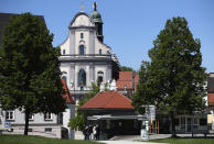 """People across the main square 'Kapellplatz"""" in front of the St. Anna basilica in Altoetting, some 90 kilometers (about 55 miles) east of Munich, Germany, Thursday, May 7, 2020. """"The heart of Bavaria and one of the hearts of Europe"""". Pope emeritus Benedict XVI. said. The city is one of the 'Shrines of Europe', the seven most important Marian pilgrimage sites in Europe. The 'Graminger Weissbraeu' brewery and traditional Bavarian restaurant, which has been in the same family for a century, is preparing to welcome guests back to its restaurant for the first time in two months — with new rules and fears for the future. (AP Photo/Matthias Schrader)"""