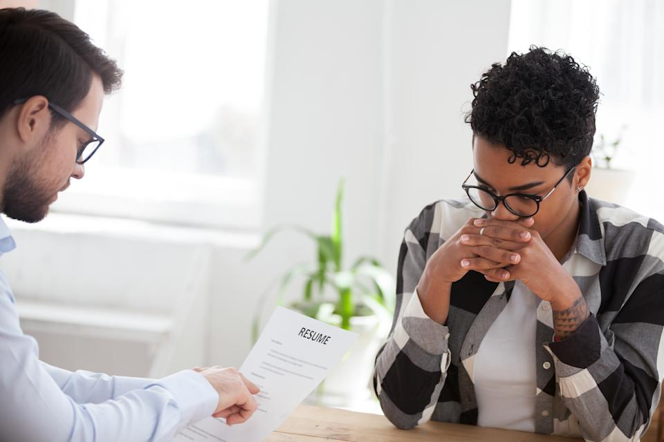 Two people sitting at the desk in office room. Advisor holding pointing at resume paper, stressed diffident African candidate woman during interview. Human resources, recruitment and hiring concept