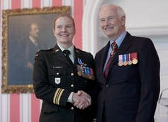 A woman in military garb shakes hands with the governor general.