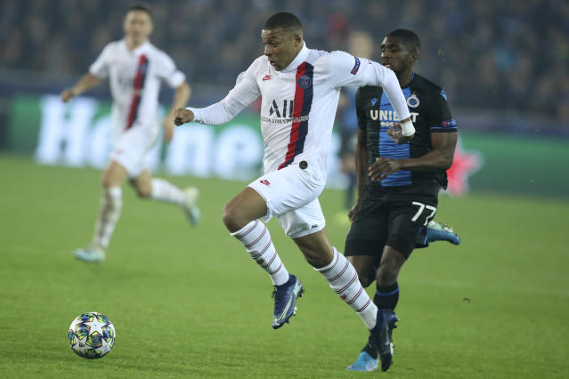 PSG's Kylian Mbappe, center, goes after the ball as he is chased by Brugge's Clinton Mata, right, during a Champions League Group A soccer match between Club Brugge and Paris Saint Germain at the Jan Breydel stadium in Bruges, Belgium, Tuesday, Oct. 22, 2019. (AP Photo/Francisco Seco)