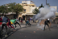Demonstrators run after rioT police fired a stone grenade during protests against the arrest of opposition leader and former presidential candidate Ousmane Sonko, Senegal, Monday, March 8, 2021. Senegalese authorities have freed opposition leader Ousmane Sonko while he awaits trial on charges of rape and making death threats. The case already has sparked deadly protests threatening to erode Senegal's reputation as one of West Africa's most stable democracies. (AP Photo/Leo Correa)