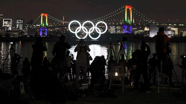 PHOTO: Journalists take images of the illuminated Olympic Rings monument at Odaiba Marine Park as the Rainbow Bridge is illuminated in rainbow colors to mark half a year before the opening of the Tokyo 2020 Olympic Games in Tokyo, Japan, Jan. 24, 2020. (Kimimasa Mayama/EPA via Shutterstock)