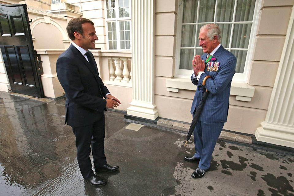 Charles Moves As Emmanuel Macron Touches His Arm