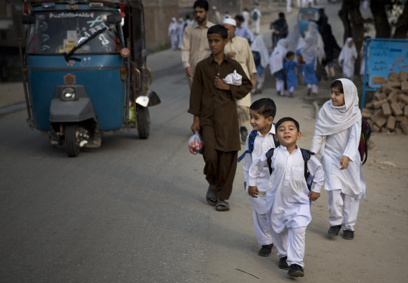In this Saturday, Oct. 5, 2013 photo, Pakistani children on their way to school in Mingora, Swat Valley, Pakistan. A year ago Pakistani girl Malala Yousufzai was shot in the head by a Taliban attacker in Mingora on her way home from school, Malala remains in Britain and her assailant is still at large, police say the case is closed. And many Pakistanis publicly wonder whether the shooting was staged to create a hero for the West to embrace. (AP Photo/Anja Niedringhaus)