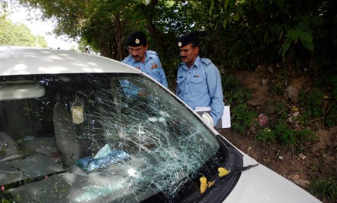 Security officials inspect the damaged car, which prosecutor Chaudhry Zulfikar was traveling in when he came under attack on May 3.