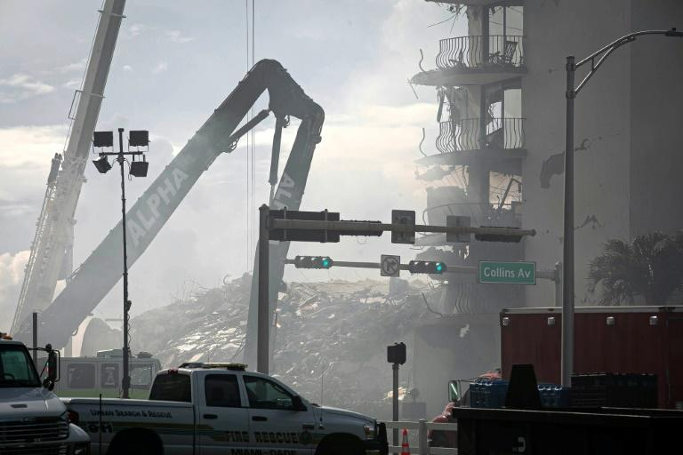 Construction equipment removes rubble at the site of the collapsed building in Surfside, Florida, on June 26, 2021