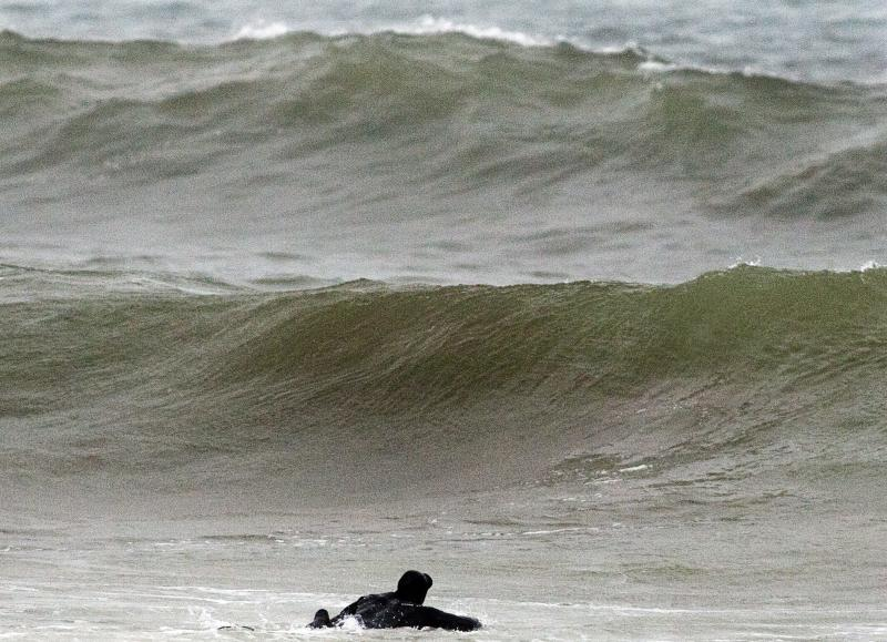 A surfer paddles out into waves generated by Tropical Storm Leslie, at Lawrencetown Beach near Halifax, Novascotia, on Sunday, Sept. 9, 2012. Leslie is expected to make landfall in Newfoundland early in the week bringing heavy rain and high winds. (AP Photo/The Canadian Press, Andrew Vaughan)