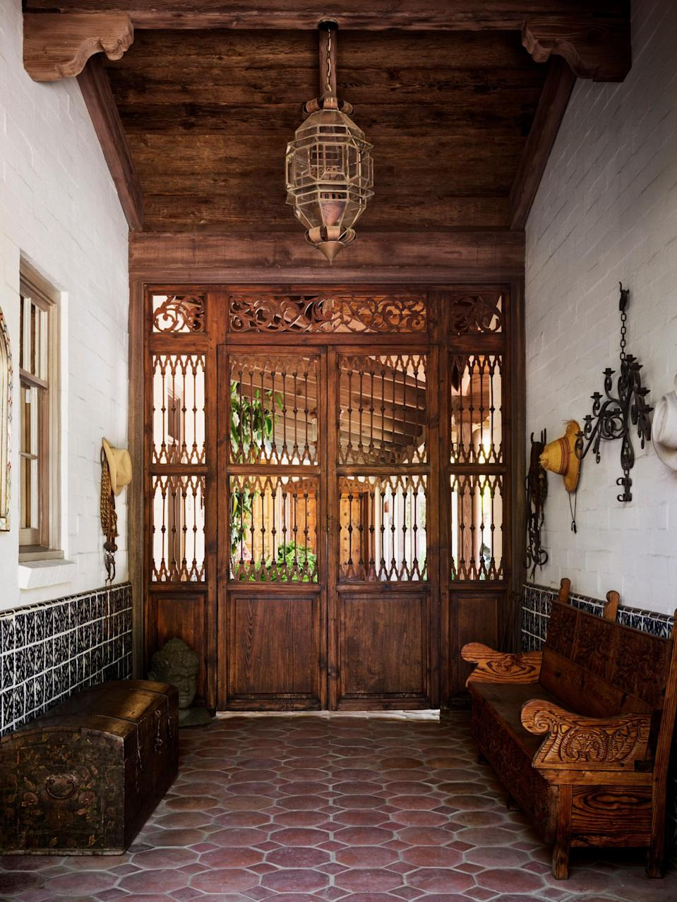 """Actor Rainn Wilson and his wife, writer Holiday Reinhorn, were immediately enchanted by this Alfred """"Hap"""" Gilman–designed Spanish-style hacienda with distant views of the Pacific Ocean. After buying the property, they turned to decorator Tammy Randall Wood to help them realize their vision. The house's entry arcade features antique wood gates and beams from Gaudalajara."""