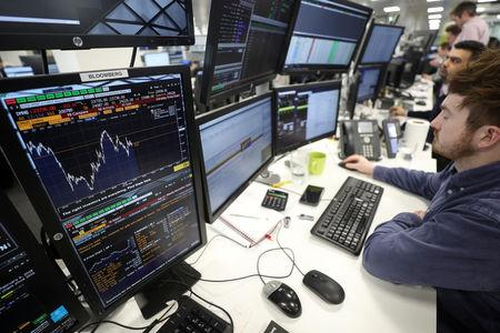 FILE PHOTO:  Traders looks at financial information on computer screens on the IG Index trading floor