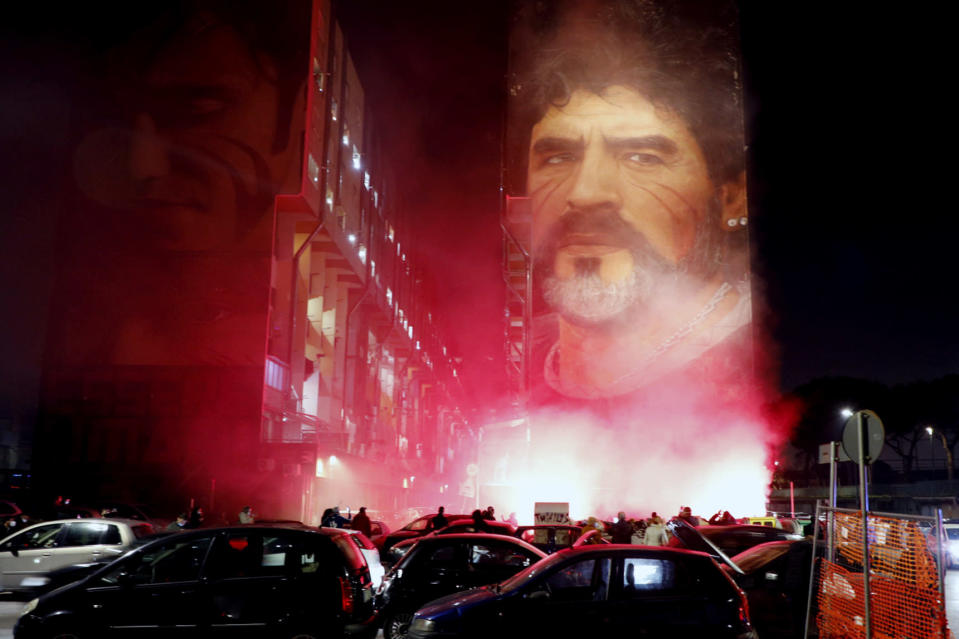 People light flares as they gather under a mural depicting soccer legend Diego Maradona, in Naples, Italy, Wednesday, Nov. 25, 2020. Diego Maradona has died. The Argentine soccer great was among the best players ever and who led his country to the 1986 World Cup title before later struggling with cocaine use and obesity. He was 60. (Fabio Sasso/LaPresse via AP)
