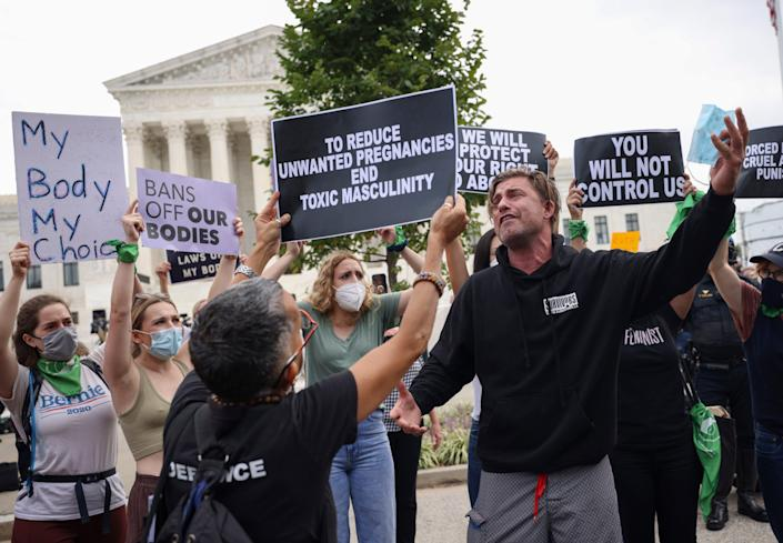 Pro-choice and anti-abortion activists protest alongside each other during a demonstration outside of the Supreme Court on October 04, 2021.