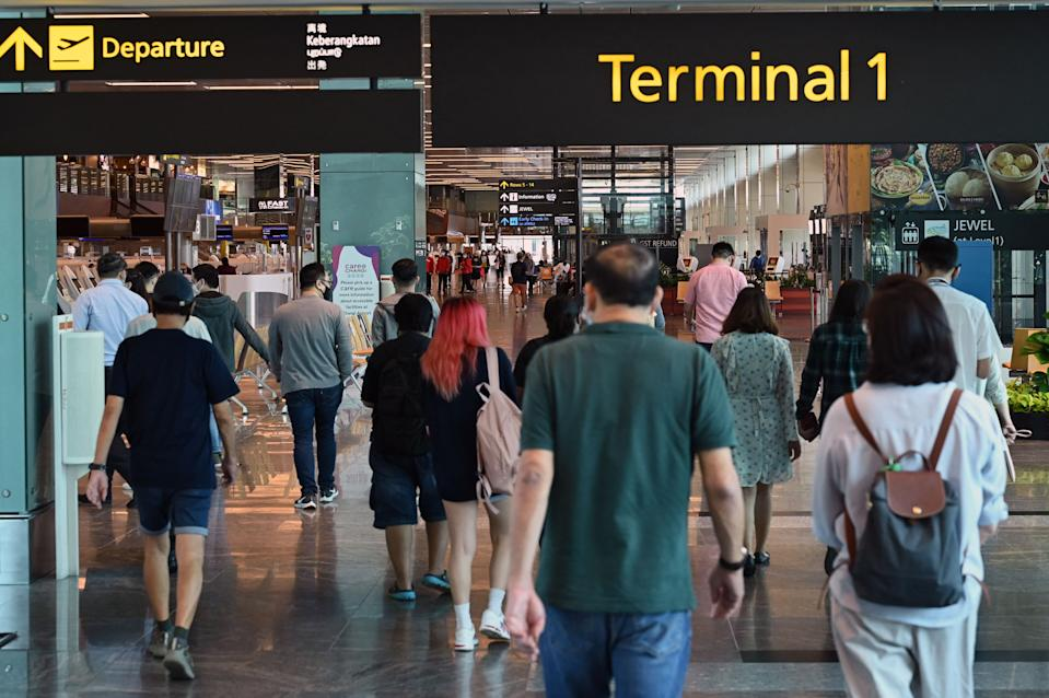 People seen at the departure hall of Changi Airport on 15 March. (PHOTO: Getty Images)