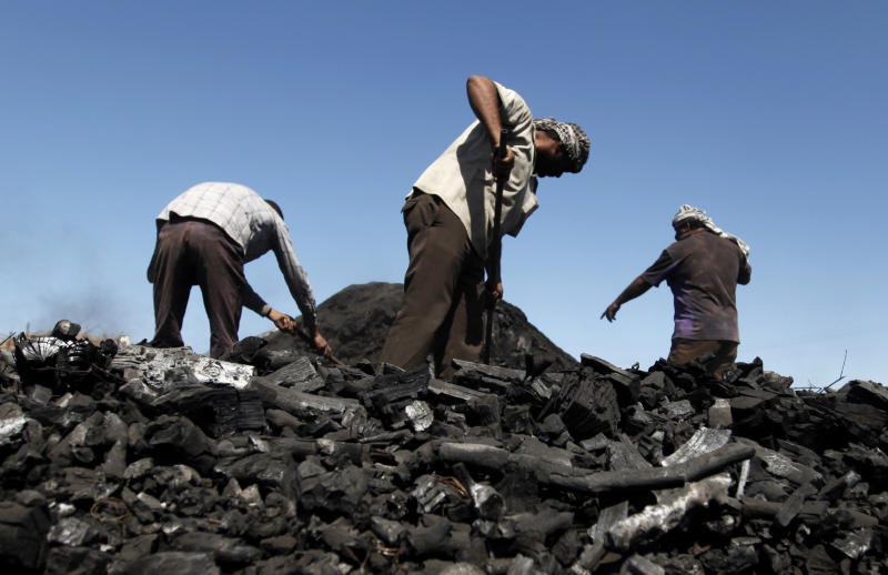 In this Sunday, March. 24, 2013 photo, Palestinian workers remove coal from a pile at one of the few local charcoal manufacturing shops east of Gaza City. In adapting to years of border blockades and shortages, Gazans have become experts at recycling and making new out of old, including turning scrap wood into charcoal to be used for barbecue grills and water pipes in local restaurants and coffee houses. (AP Photo/Hatem Moussa)