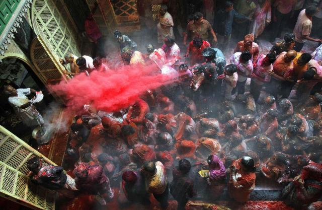 A Hindu priest (L) throws coloured powder at the devotees during Holi celebrations at Shamlal Ji temple in Kolkata March 17, 2014. Holi, also known as the Festival of Colours, heralds the beginning of spring and is celebrated all over India. REUTERS/Rupak De Chowdhuri (INDIA - Tags: RELIGION SOCIETY)