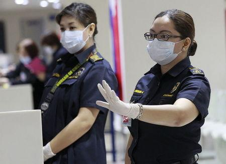 A customs inspector wearing a face mask gestures as she waits for flight passengers arriving from South Korea at the arrival area of Ninoy Aquino International Airport in Manila