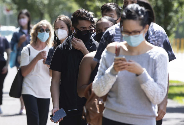 People wait in line at a COVID-19 testing facility during the coronavirus pandemic in Burnaby, British Columbia, on Thursday, Aug. 13, 2020. (Darryl Dyck/The Canadian Press via AP)