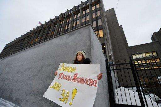 "<p>A young woman holds a poster reading: ""We support the Dima Yakovlev bill"" outside the upper house of Russia's parliament, the Federation Council, early on December 26, 2012. Russia's upper house of parliament on Wednesday unanimously backed a bill barring Americans from adopting Russian children, leaving the controversial measure in the hands of President Vladimir Putin.</p>"