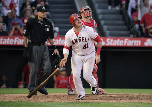 Los Angeles Angels' Justin Bour watches his three-run home run, near Cincinnati Reds catcher Curt Casali, right, and home plate umpire Pat Hoberg during the eighth inning of a baseball game Wednesday, June 26, 2019, in Anaheim, Calif. (AP Photo/Mark J. Terrill)