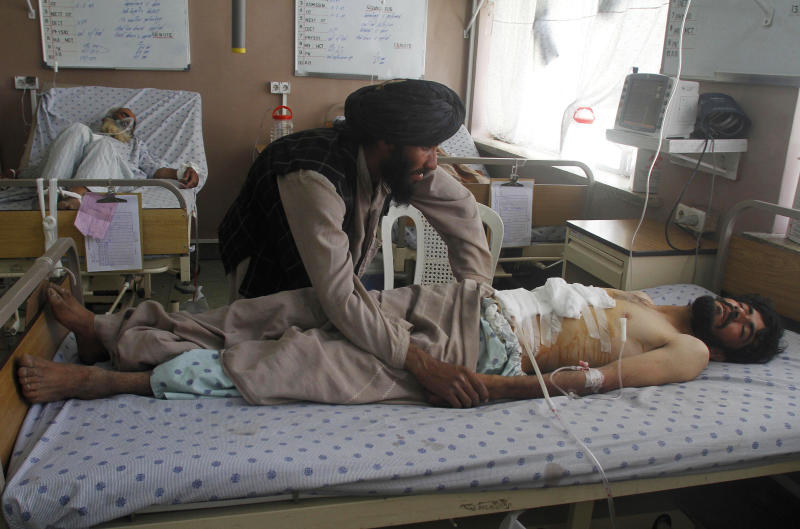 An Afghan man attends to an injured man at the hospital in Kandahar, Afghanistan, Wednesday, May 8, after a demonstration to protest a joint raid by coalition and Afghan forces turned deadly killing and wounding several. Villagers from Kandahar's Maiwand district are charging police with opening fire on hundreds of protesters denouncing raids two days earlier by Afghan and coalition forces. (AP Photo/Allauddin Khan)