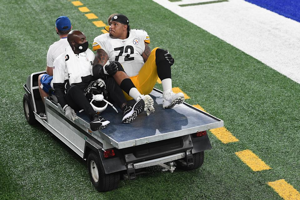 Zach Banner holds back tears as he rides off the field in a cart.