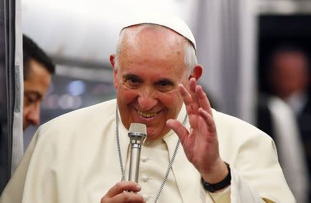 Pope Francis gestures as he speaks with journalists on the flight back from Istanbul to Rome