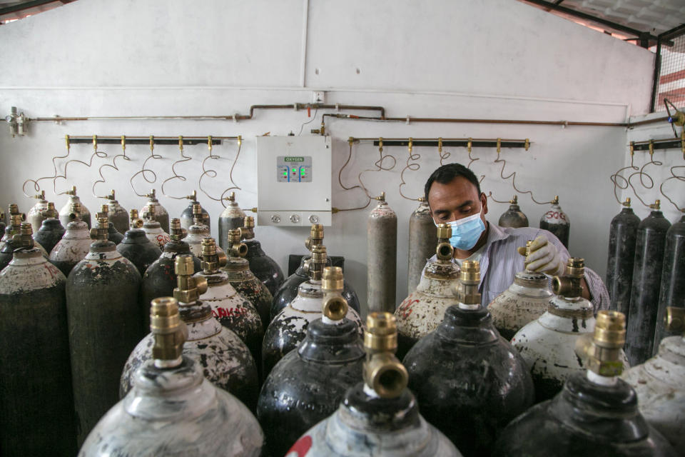 Staff member of a government run hospital checks to refill the empty oxygen cylinders in Kathmandu, Nepal, Friday, May 7, 2021. Across the border from a devastating surge in India, doctors in Nepal warned Friday of a major crisis as daily coronavirus cases hit a record and hospitals were running out of beds and oxygen. (AP Photo/Niranjan Shrestha)