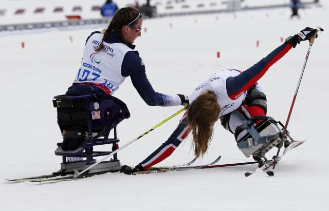 Tatyana McFadden of the U.S. helps Norway's Birgit Skarstein (R) in the finish area during the women's 12 km cross-country sitting at the 2014 Sochi Paralympic Winter Games in Rosa Khutor March 9, 2014. REUTERS/Alexander Demianchuk (RUSSIA - Tags: SPORT OLYMPICS SKIING)