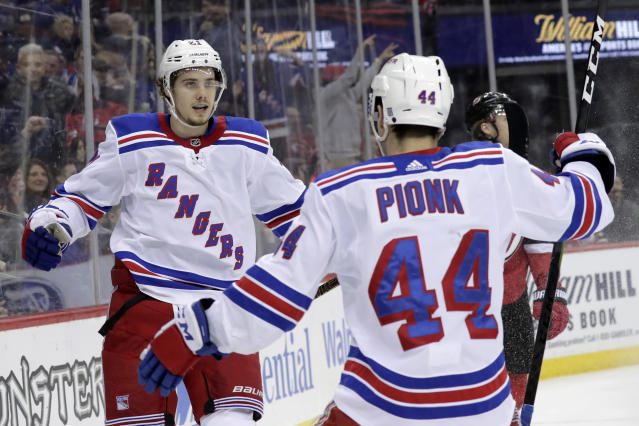 New York Rangers center Brett Howden, left, celebrates after scoring a goal on the New Jersey Devils with teammate Neal Pionk (44) during the first period of an NHL hockey game, Monday, April 1, 2019, in Newark, N.J. (AP Photo/Julio Cortez)