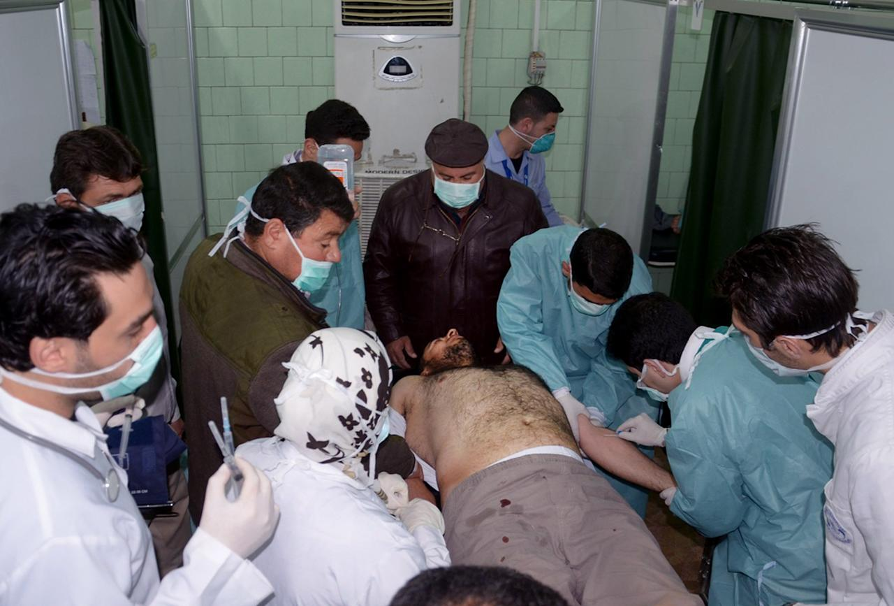 FILE - In this Tuesday March 19, 2013 file photo released by the Syrian official news agency SANA, a Syrian victim who suffered an alleged chemical attack at Khan al-Assal village according to SANA, receives treatment by doctors, at a hospital in Aleppo, Syria. The purported instances in which chemical weapons have been used in Syria have been relatively small in scale: nothing along the lines of Saddam Hussein's 1988 attack in Kurdish Iraq. That raises the question of who would stand to gain as President Bashar Assad's regime and the opposition trade blame for the alleged attacks and definitive proof remains elusive. Analysts say the answer could lie in the past the regime has a pattern of gradually introducing a weapon to the conflict to test the international community's response. (AP Photo/SANA, File)