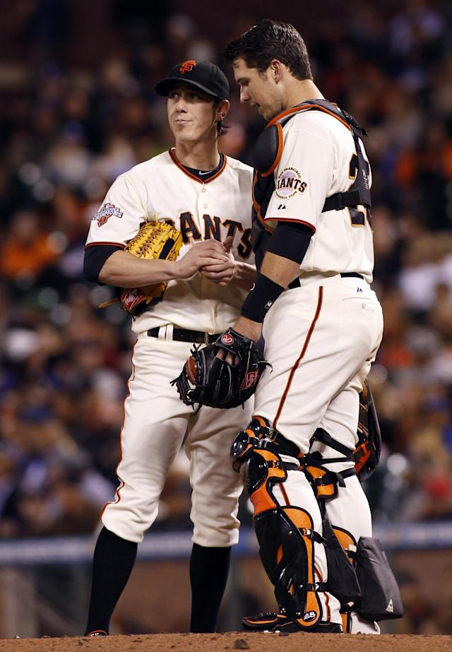 San Francisco Giants' Buster Posey, right, talks with Tim Lincecum during the fourth inning of a baseball game against the Los Angeles Dodgers in San Francisco, Thursday, Sept. 26, 2013. (AP Photo/George Nikitin)