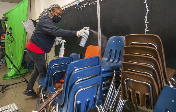 FILE - In this March 4, 2021 file photo, Latisha Bledsoe cleans chairs in the music room at Manchester Academic Charter School, during the coronavirus pandemic, in Pittsburgh. U.S. guidelines that say students should be kept 6 feet apart in schools are receiving new scrutiny from federal health experts, state governments and education officials working to return as many children as possible to the classroom. (Andrew Rush/Pittsburgh Post-Gazette via AP, File)