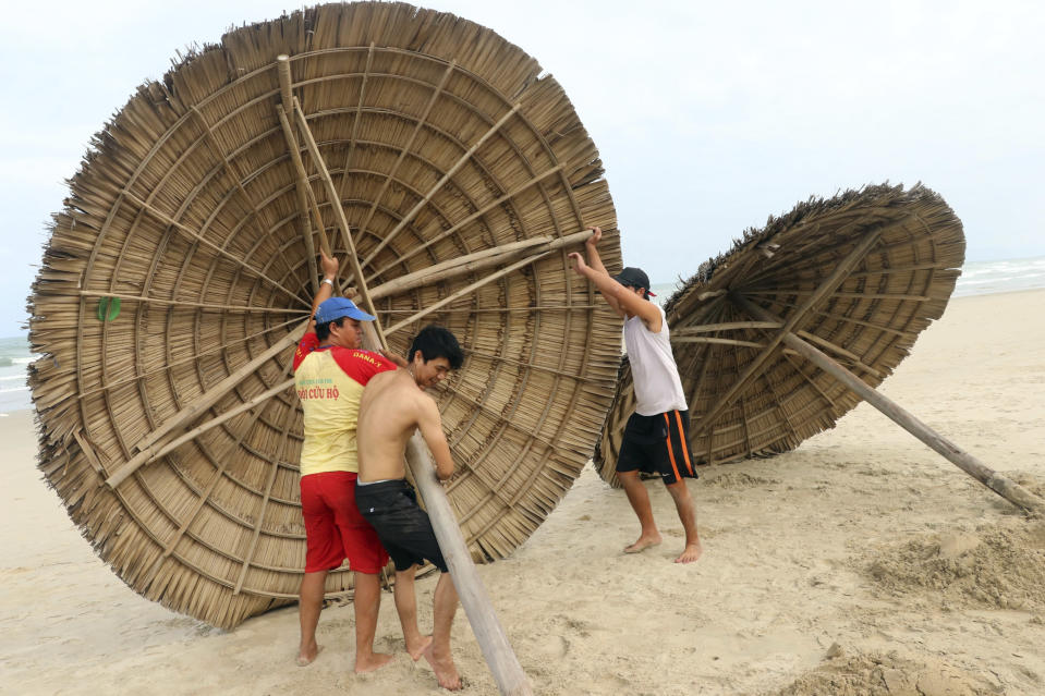 People remove beach cabanas ahead of Typhoon Molave in Danang, Vietnam on Monday, Oct. 26, 2020. National agency forecasts the typhoon to hit Vietnam on Wednesday morning in the central region where 1.3 people could face evacuation. (Tran Le Lam/VNA via AP)