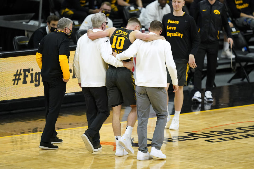 Iowa guard Joe Wieskamp (10) is helped off the court after getting injured during the first half of an NCAA college basketball game against Wisconsin, Sunday, March 7, 2021, in Iowa City, Iowa. (AP Photo/Charlie Neibergall)