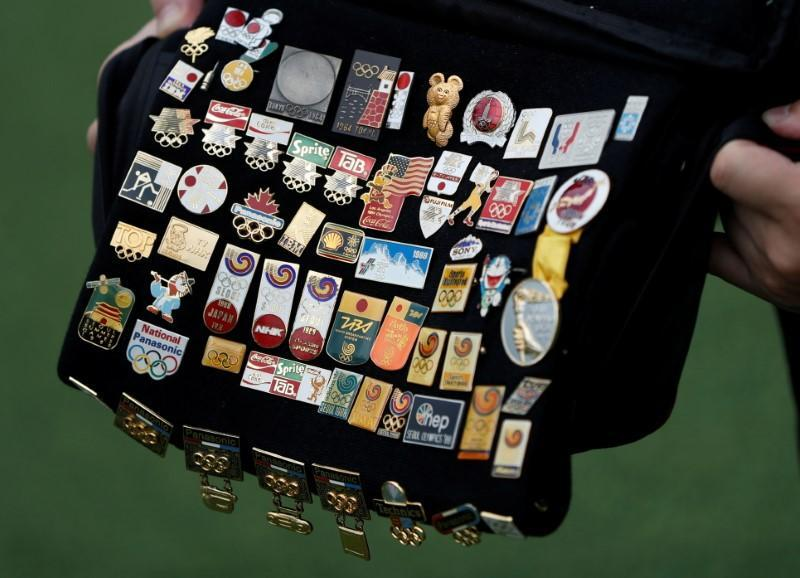 Yoshiyuki Terajima, a pin collector based in Tokyo, shows his Olympic pin collection near the National Stadium in Tokyo